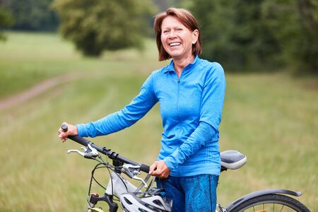 Active senior woman is doing a nature bike ride in her spare time in summer 版權商用圖片