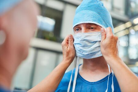 Doctor as a surgeon in blue surgical gown with surgical mask in emergency room of the clinic 免版税图像