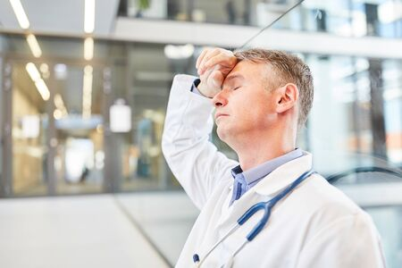 Doctor stands exhausted with his hand on his forehead in the emergency department in the hospital