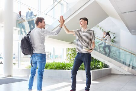 Two friends share High Five as students in university building Stock fotó