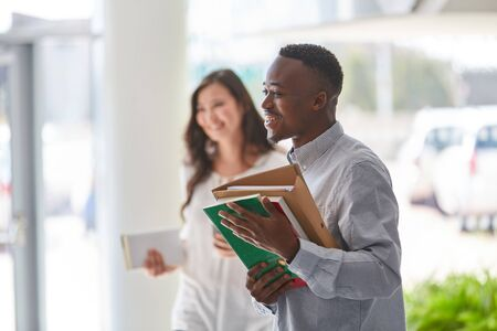 African student with books smiles with joy in university