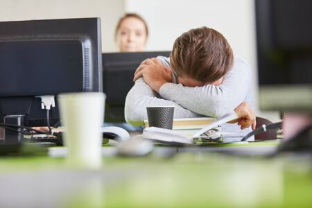 Tired or exhausted student sleeps in university classroom with computer Stock fotó