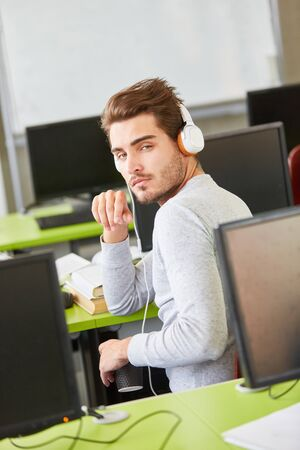 Tired IT student makes an informatics course and wears headphones Stock fotó