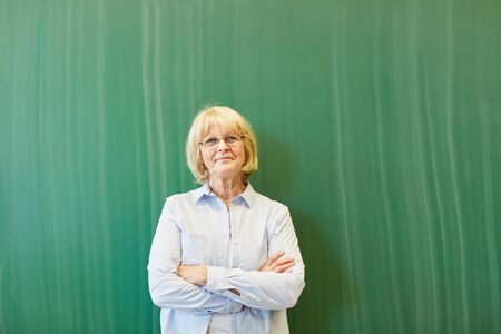 Senior woman as teacher with green chalkboard behind her
