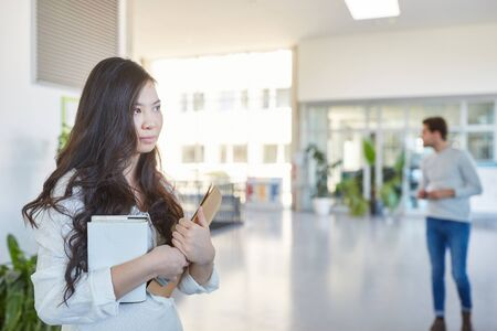 Young asian student in university hallway holds her books Stock fotó
