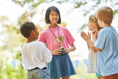 Asian girl wins a cup after the competition