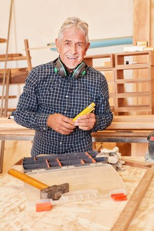 Senior man as a successful craftsman at the workbench in his joinery