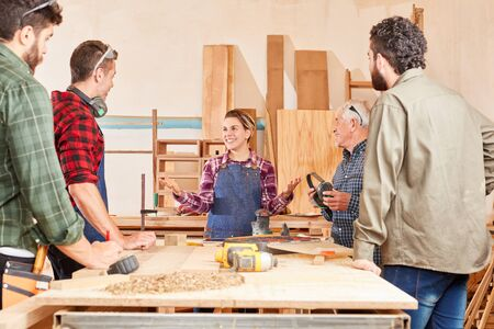 Young woman as a trainee in the joinery learns and works with colleagues in the team Stok Fotoğraf