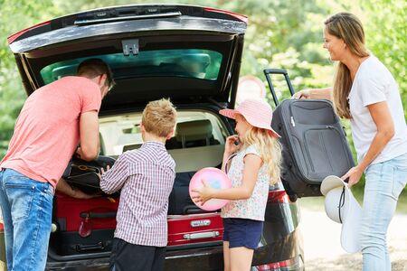 Familia con niños juntos empacando maletas en el coche antes de viajar de vacaciones Foto de archivo