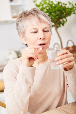 Ältere Frau, die zu Hause Medikamententabletten einnimmt Standard-Bild