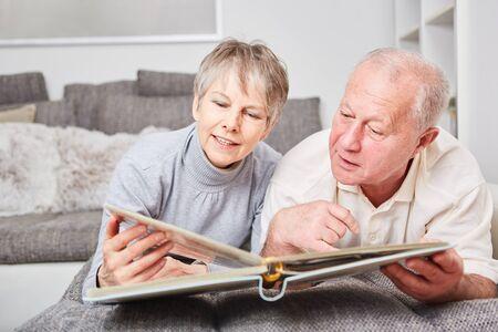Senior couple of citizens with photo album on the couch Foto de archivo - 129922187