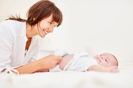 Madre sonriente cambia los pañales con su bebé recién nacido
