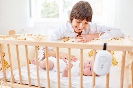 Glückliche Mutter streichelt liebevoll das Baby beim Einschlafen im Kinderbett
