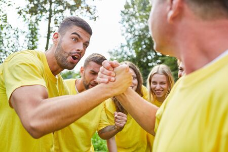 Astonished man arm wrestling in a competition at the teambuilding event