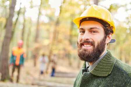 Forest worker or forestry worker smiles contentedly while working in the forest Stock Photo