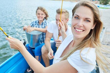 Joyful woman fishing with the family together in the boat on a lake