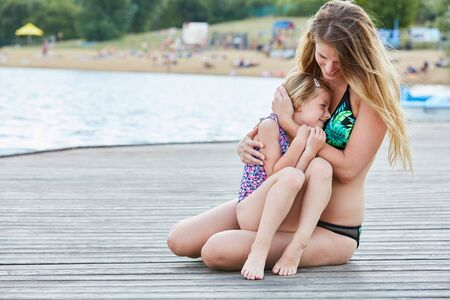 Mother and daughter lovingly hug each other on a jetty on vacation by the sea Stockfoto