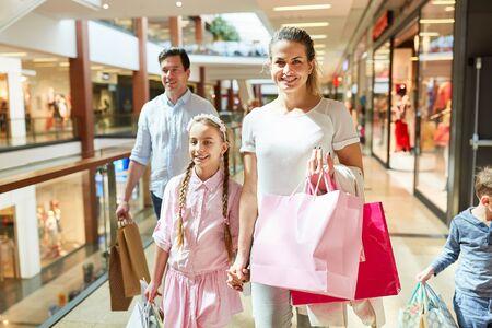 Felices padres e hijos de compras en la galería comercial