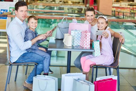 Family and children with many shopping bags and smartphone in shopping arcade