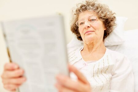 Senior woman as a patient in hospital or nursing home reads a magazine