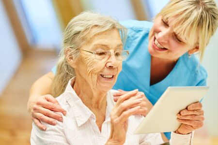 Senior woman is learning how to use tablet computer and has help from geriatric nurse