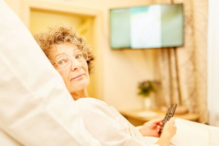 Old woman in retirement home or senior citizen apartment lies in bed watching tv Archivio Fotografico