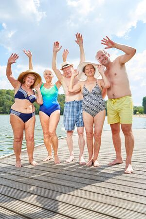 Cheerful group of vital seniors on a jetty at the lake in summer on vacation Imagens