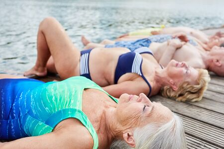 Group of seniors lying relaxed on a jetty on the lake in summer on vacation