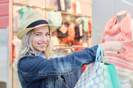 Young blond woman while shopping for clothes in front of a fashion store Stock fotó