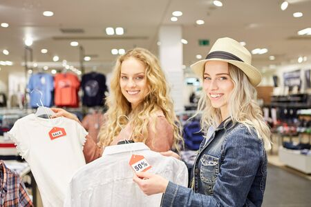 Young women as customers are happy about fashion and 50% off promotional price