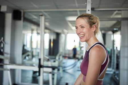 Laughing young woman in the gym has fun while exercising
