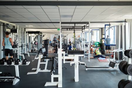 Athletes work out in the fitness center with a variety of equipment Stock fotó