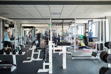 Sportowcy ćwiczą w centrum fitness z różnorodnym sprzętem Zdjęcie Seryjne