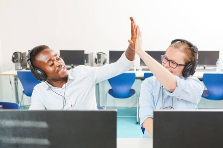 Two students with headphones on the computer in start-up business give themselves a high five