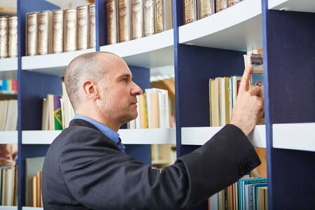 Man as lecturer or scientist looking for a book in the library for borrowing