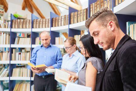 Gruppe von Menschen beim gemeinsamen Buchlesen in der Bibliothek des Community College