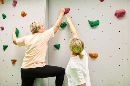 Vital senior woman climbing a climbing wall under the guidance of a physiotherapist