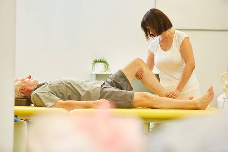 Senior as a patient in rehab gets physiotherapy on the knee joint for pain relief Imagens