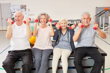 Seniors do healthy dumbbell training in rehab at the fitness center Banco de Imagens