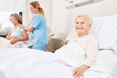 Happy senior woman in hospital bed in hospital room in nursing home