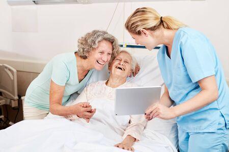 Cuidador mujer mayor feliz y visitante está apuntando a un Tablet PC Foto de archivo
