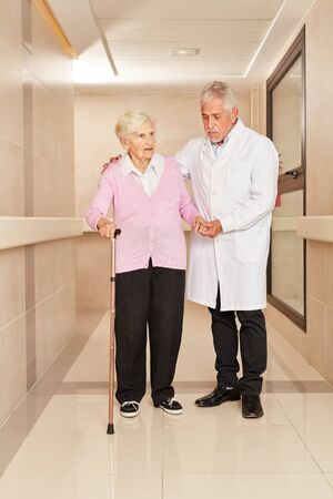 Doctor and frail old woman with crutch on the floor in the hospital