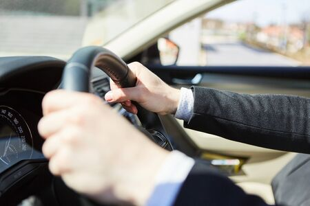 Hands of the driver on the steering wheel as a symbol of mobility