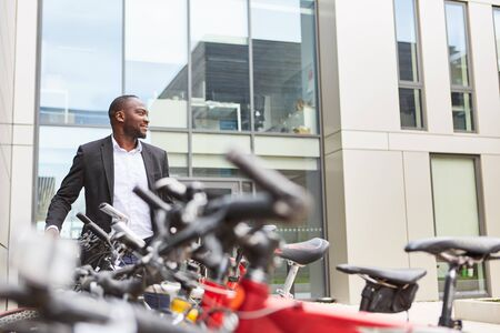 African businessman as environmentally friendly commuter by bicycle Stock fotó - 129293542