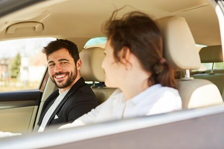 Two young business people or friends traveling by car