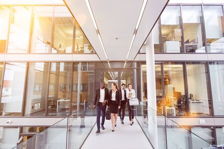Group of business people comes out of the modern office of an insurance company