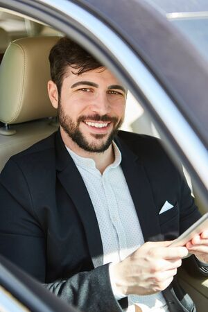 Successful business man in the car on business trip with tablet computer
