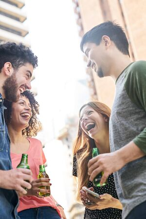 Group of students as friends have fun at a party with a bottle of beer