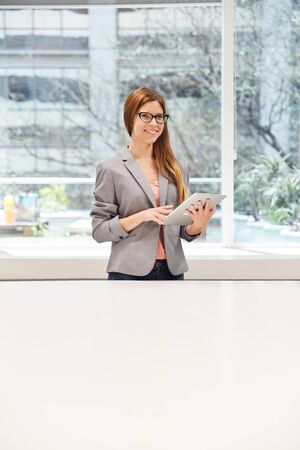 Young business woman using tablet computer works online as an intern or trainee Stock Photo