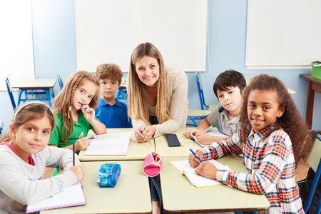 Groep multiculturele elementaire studenten in bijles met leraar Stockfoto